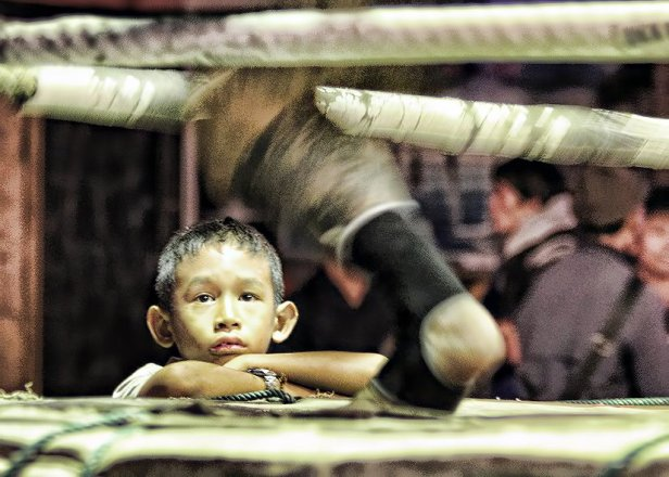 While taking pictures of a Muay Thai fight in Chaing Mai, Thailand - I got low and zoomed in on the face of this young man watching the fight from ringside
