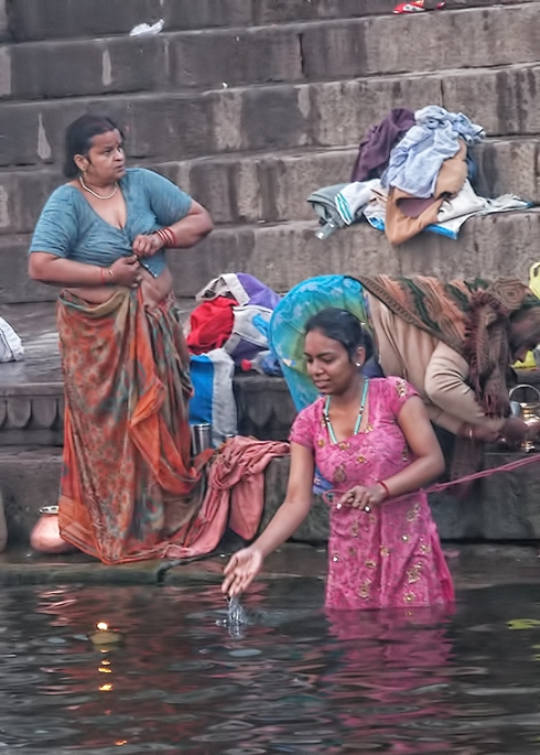 Local women bathing in the Ganges and setting candle wishes in the water